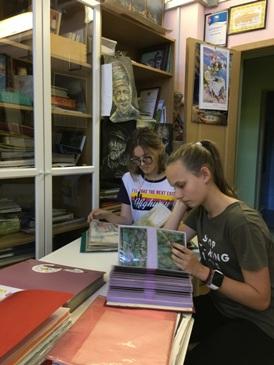 Студийцы изучают альбомы с набросками и фотографиями работ других учеников.